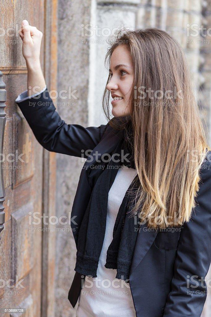 Girl knocks in closed door stock photo