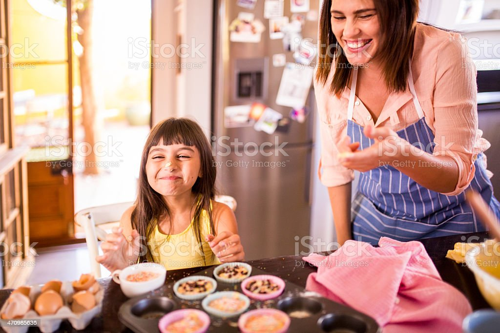 Girl laughing because her mom put dough on her nose stock photo