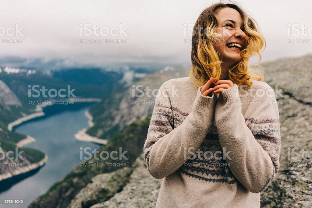 Girl laughing on the Trolltunga stock photo