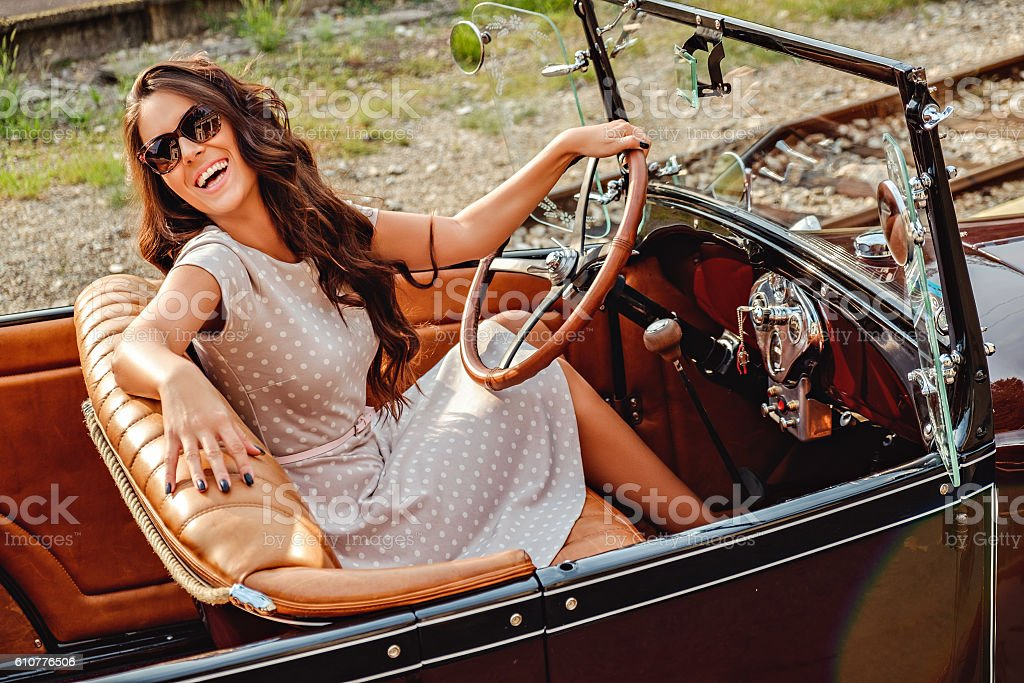 Girl laughing while driving old classic car stock photo