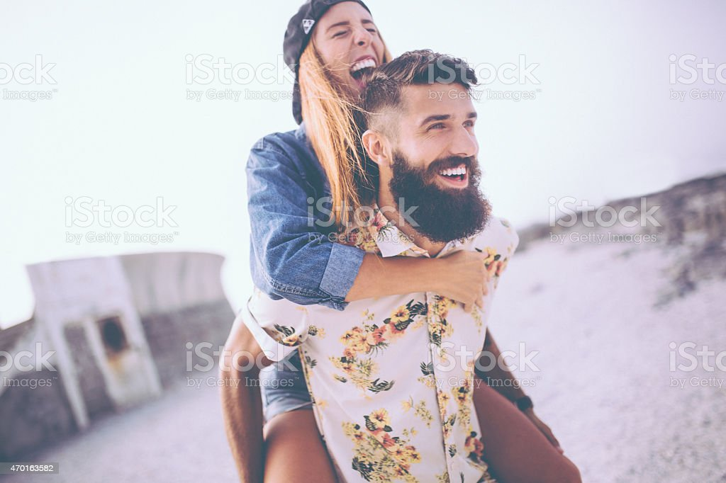 Girl laughing while hipster boyfriend piggybacks her at the beac stock photo