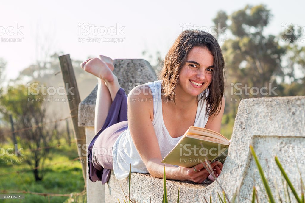 Girl Laying on wall reading stock photo