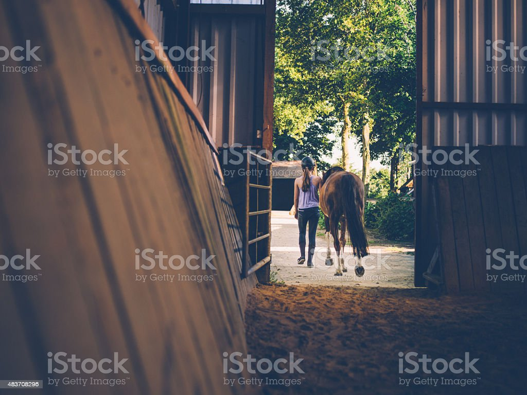Girl leading her horse out of stables with vintage feel stock photo