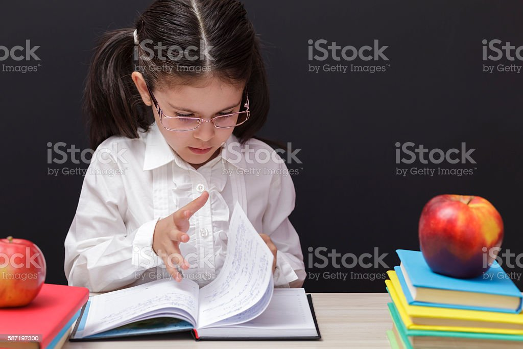 Girl Leafing Through a Book in Front of School Board stock photo