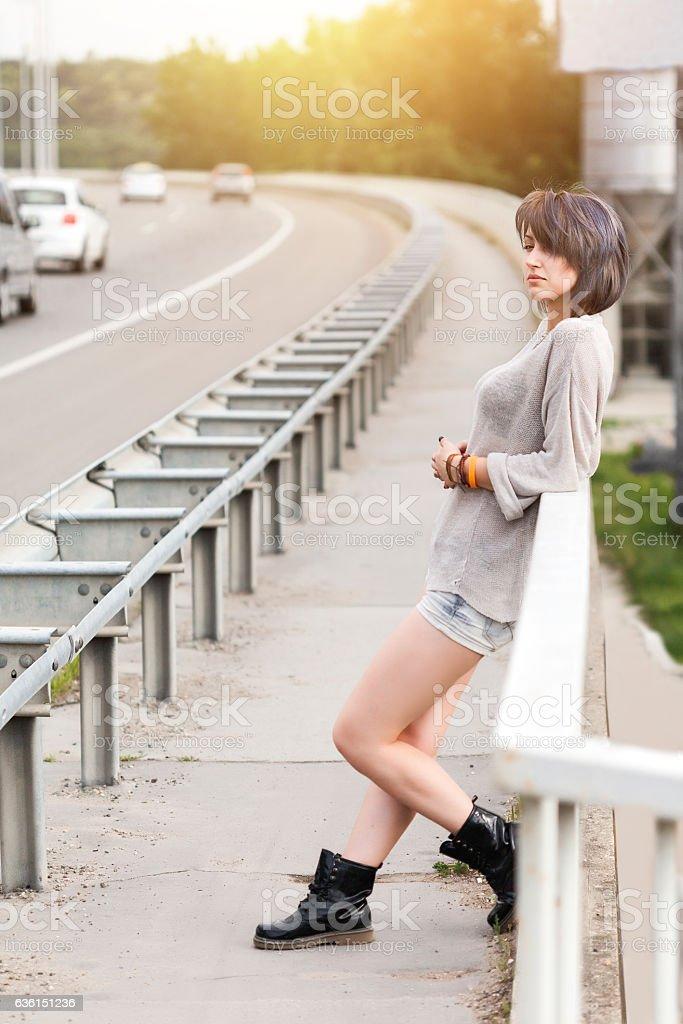 Girl leaning on bridge stock photo