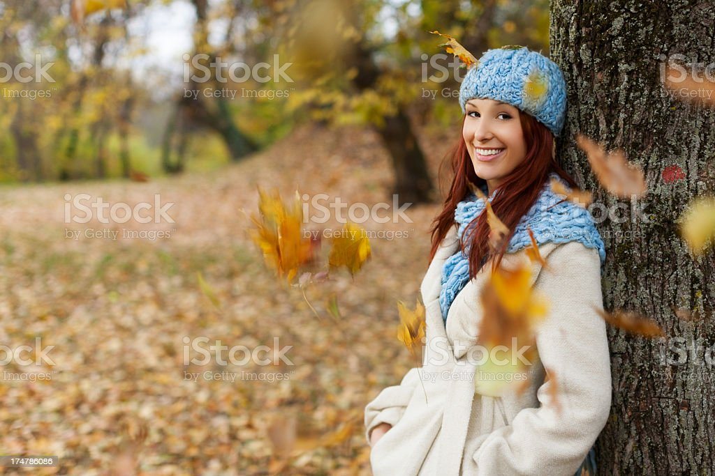 Girl leaning on tree in the park with falling leaves royalty-free stock photo