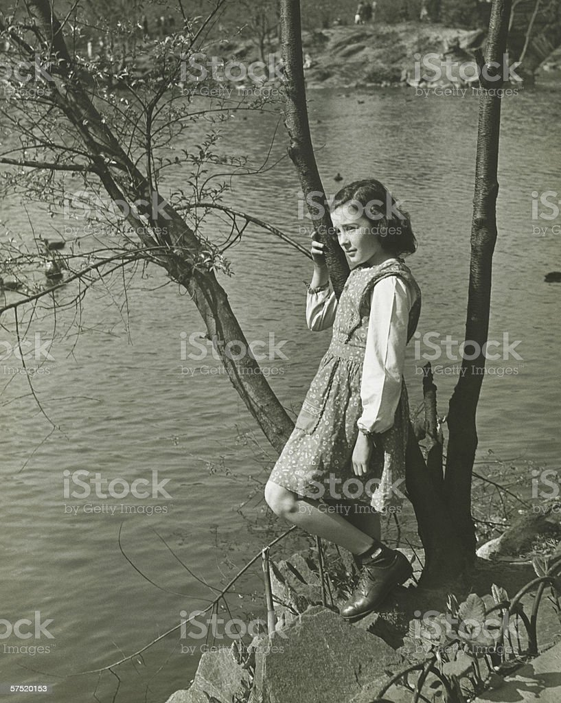 Girl (8-9) leaning on tree trunk by water, (B&W), elevated view stock photo