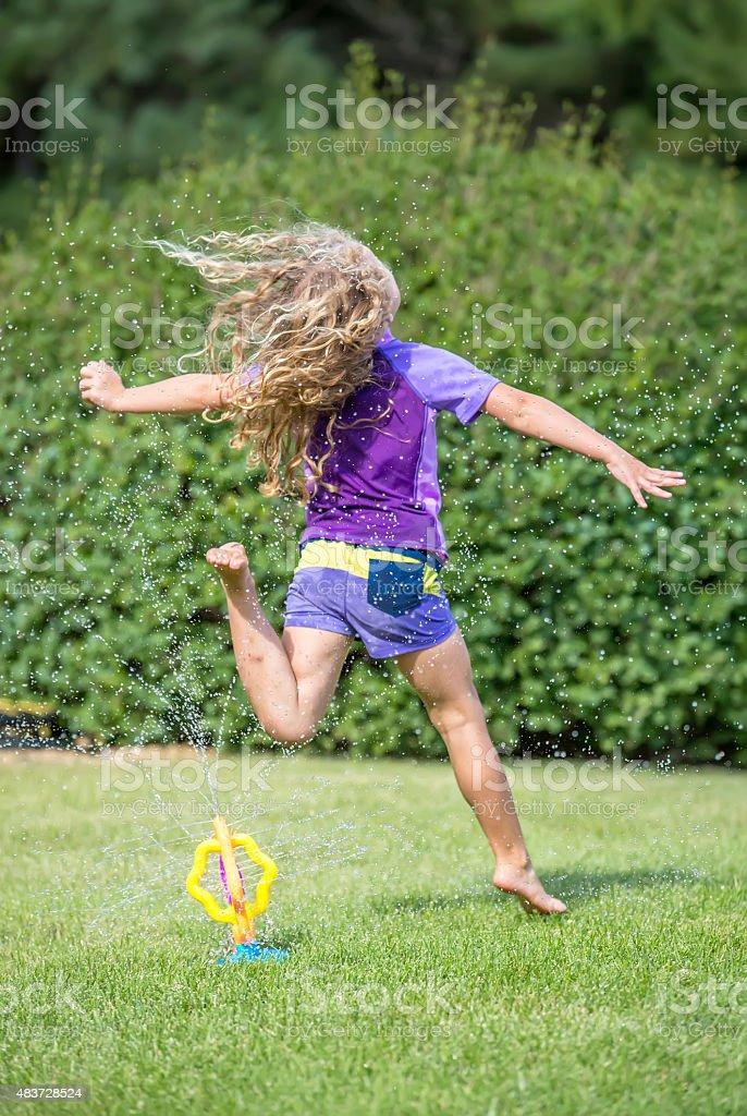 Girl Leaping Through Sprinkler Water on Summer Day stock photo
