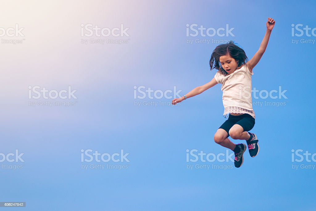 Girl leaping towards the sky stock photo
