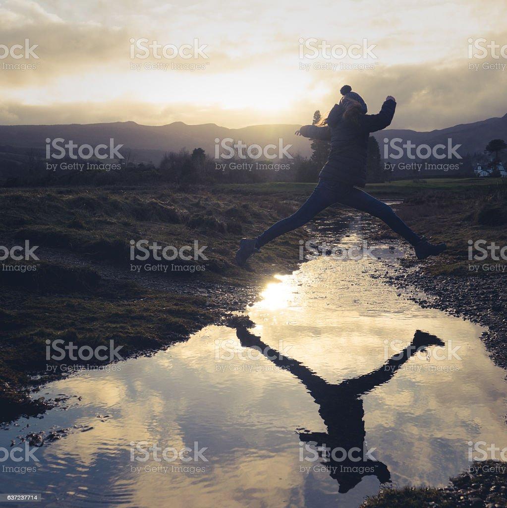 Girl Leaps Over Stream stock photo