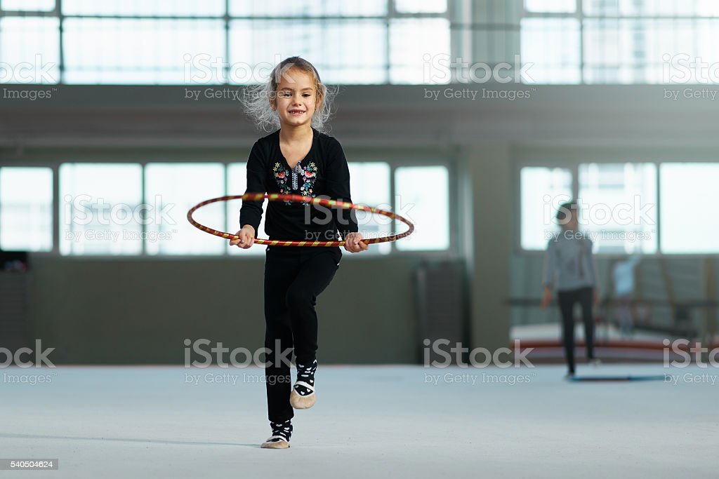 Girl learning to use  hoop in rhythmic gymnastics. stock photo