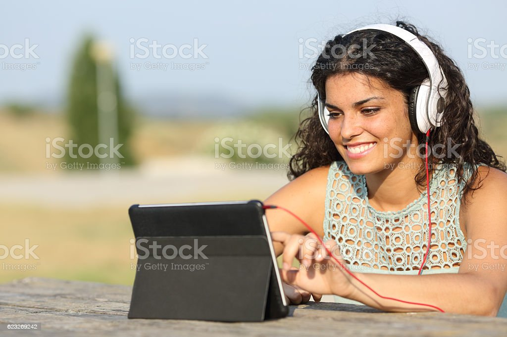 Girl learning with a tablet outdoors stock photo