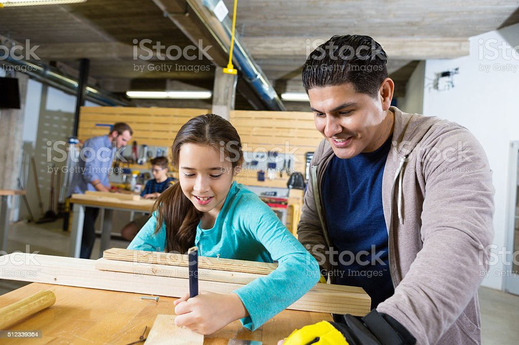 Girl learns about woodworking in day camp stock photo