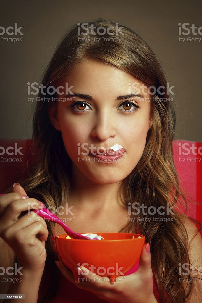 Girl licking her lips covered with yogurt stock photo