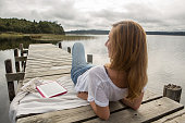 Girl lies on jetty above lake, uses digital tablet