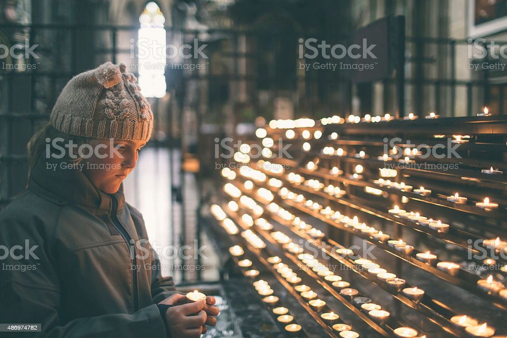 Girl lighting a candle in remembrance stock photo
