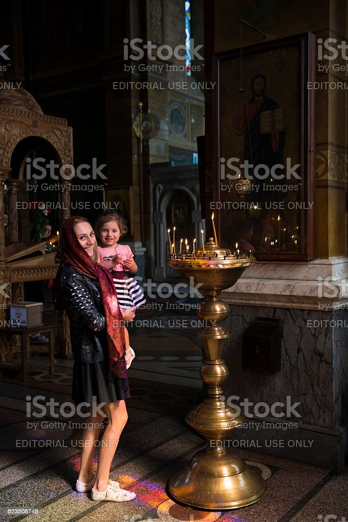 Girl lighting candle at Georgian Orthodox church in Batumi stock photo