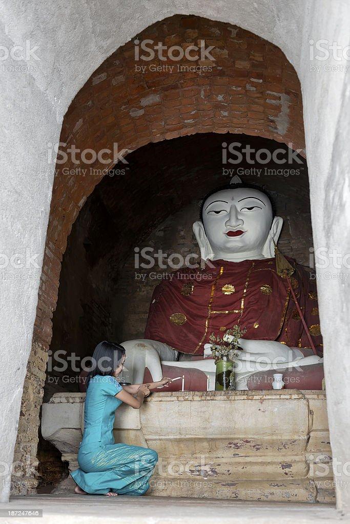 Girl Lighting Candle for Sitting Buddha royalty-free stock photo