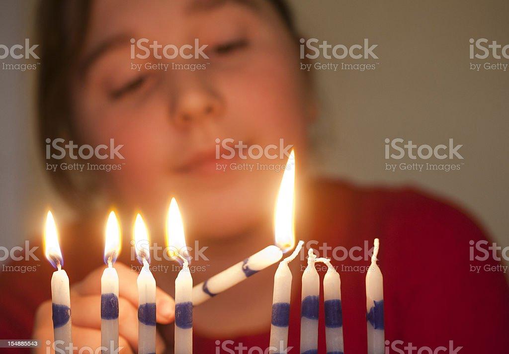Girl lights menorah stock photo