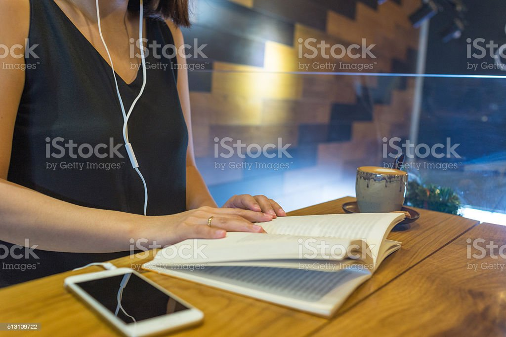 Girl listen music and reading book sitting in wooden background stock photo
