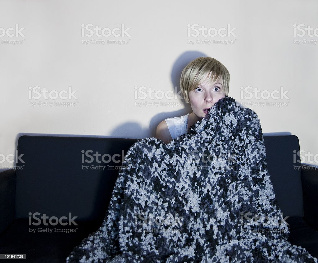 Girl listen to horror or suspense movie alone royalty-free stock photo