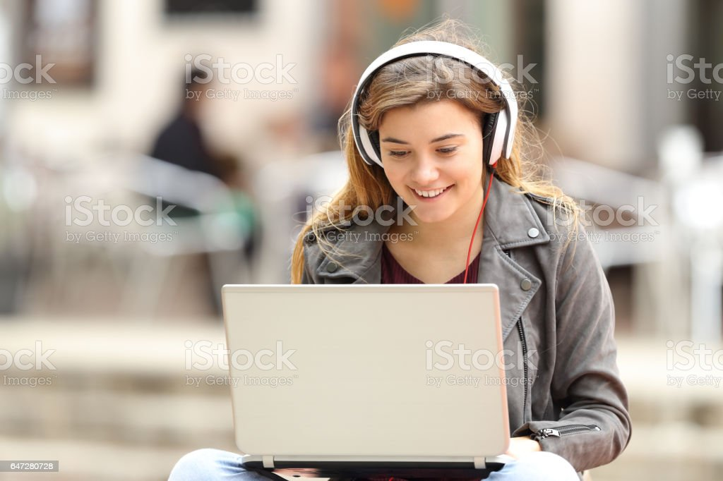 Girl listening and downloading music from laptop stock photo