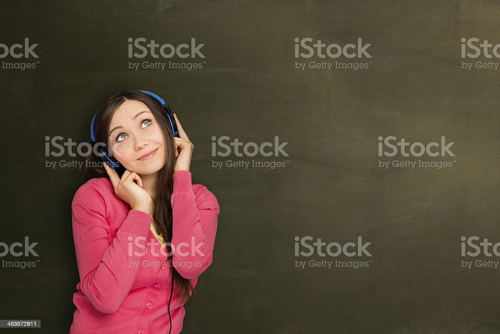 Girl listening music in front of empty blackboard. royalty-free stock photo