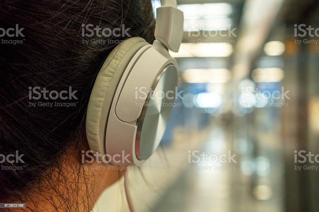 girl listening music  in subway station stock photo