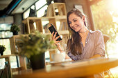 Girl listening music on mobile phone in a coffee shop