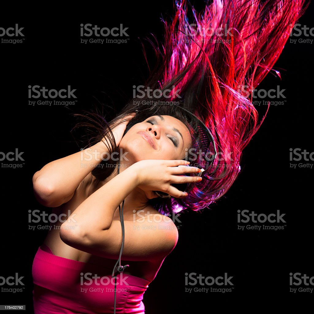 Girl listening music with Headphones on black background stock photo