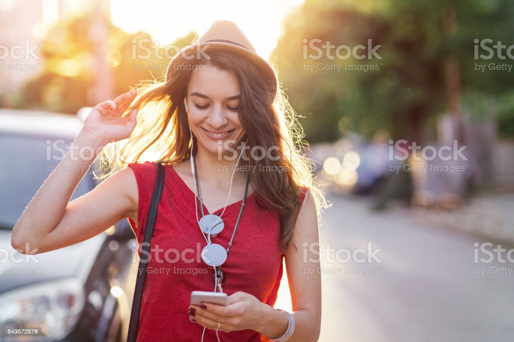 Girl listening to music and texting on a cell phone stock photo