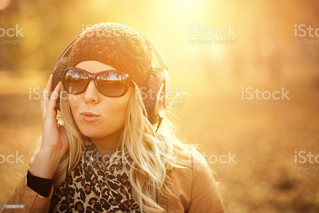 girl listening to music in the autumn sunshine royalty-free stock photo