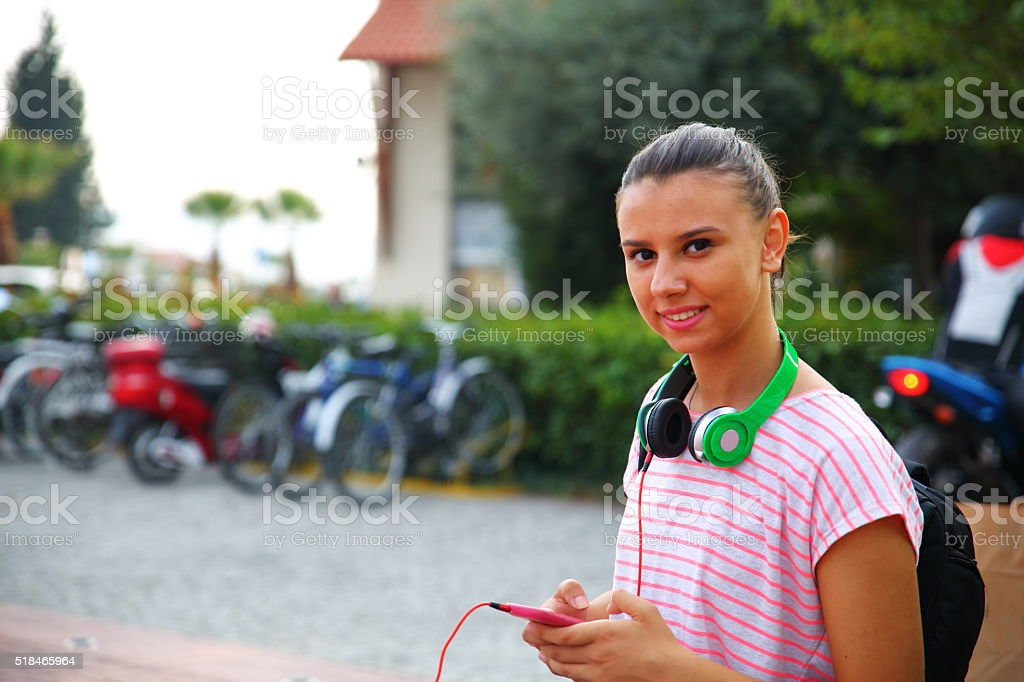 Girl Listening To Music On Headphones At Campus stock photo