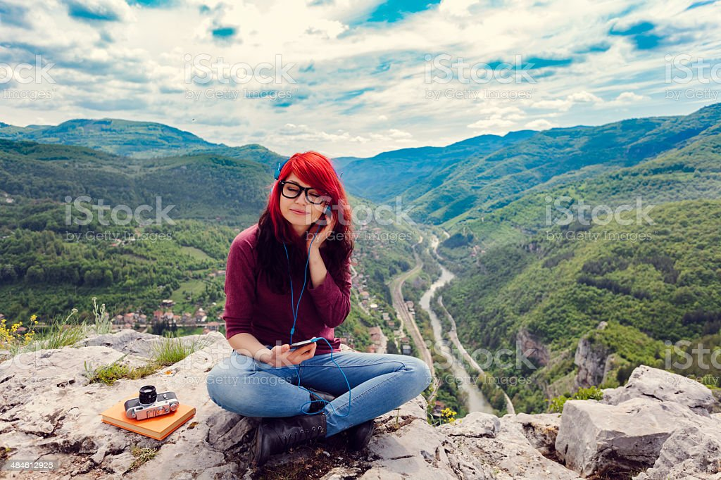 Girl listening to the music at the mountain peak stock photo
