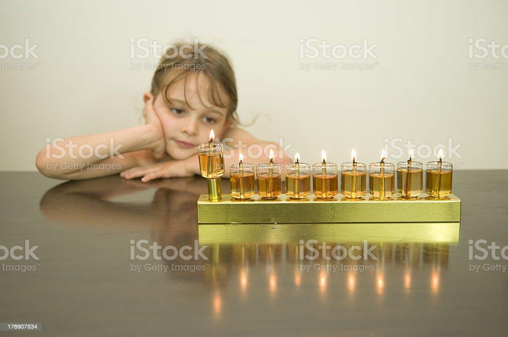 girl look at the Hanukkah menorah stock photo