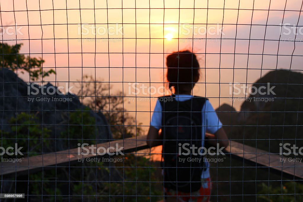 Girl look at the sunset with steel mesh background. stock photo