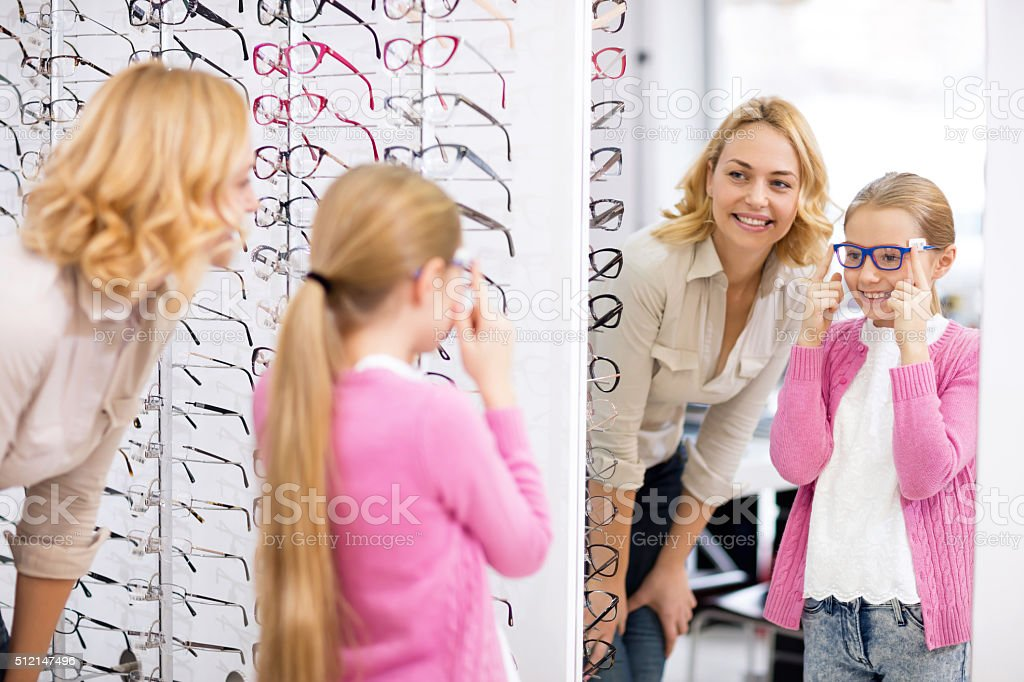 Girl look herself in the mirror with new eyeglasses stock photo