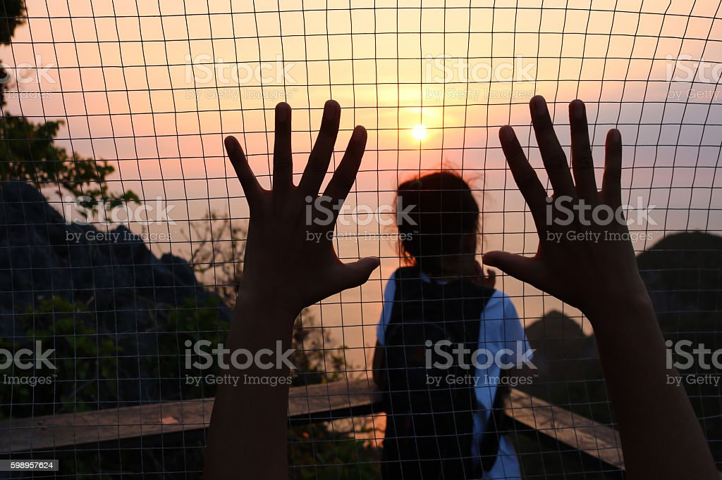 Girl look the view of sunset with steel mesh background. stock photo