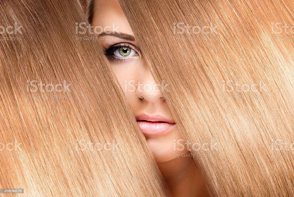 girl look through shining shiny blonde hair stock photo