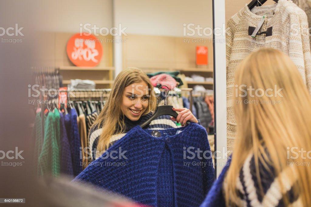 Girl looking at cardigan in mirror stock photo