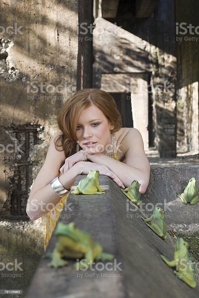 Girl looking at frogs stock photo