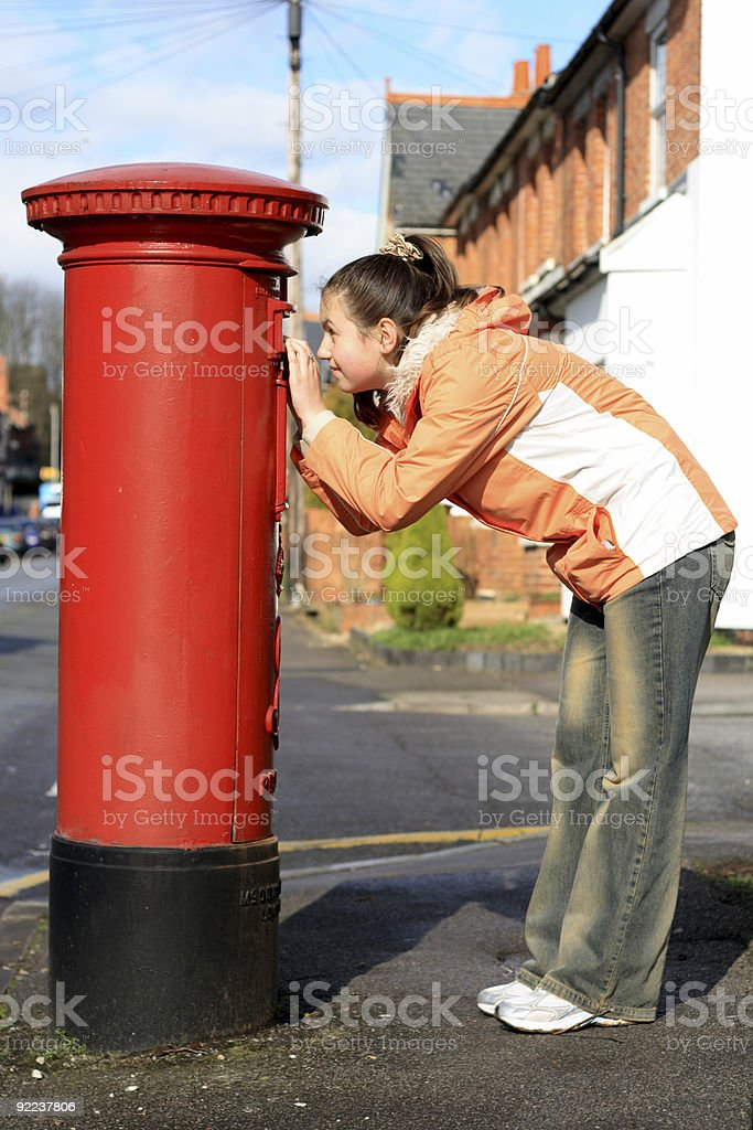 girl looking at hole of red british postbox royalty-free stock photo