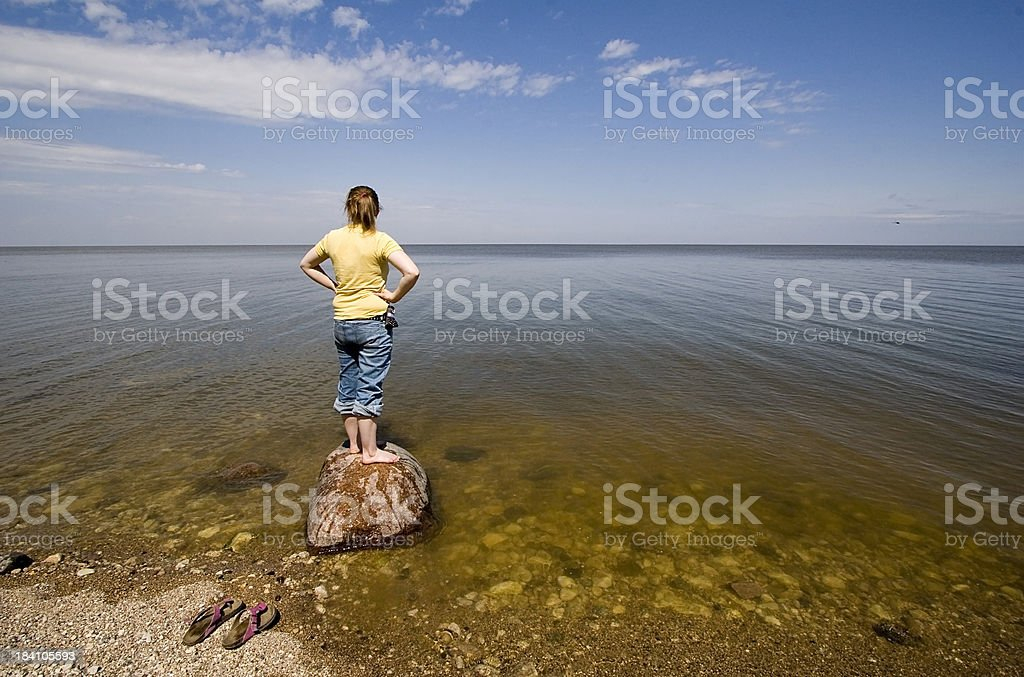 Girl looking at lake. stock photo