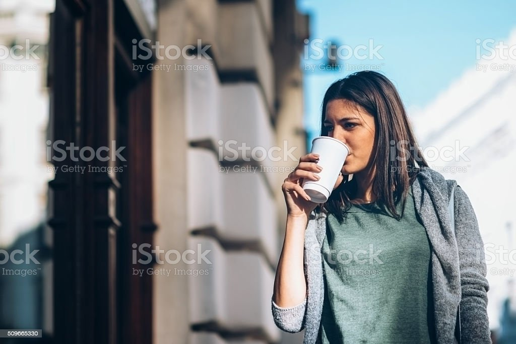 Girl looking at shop windows, sipping take-away coffee stock photo