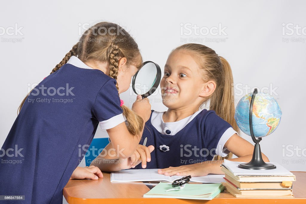 Girl looking at the other girl with a magnifying glass stock photo