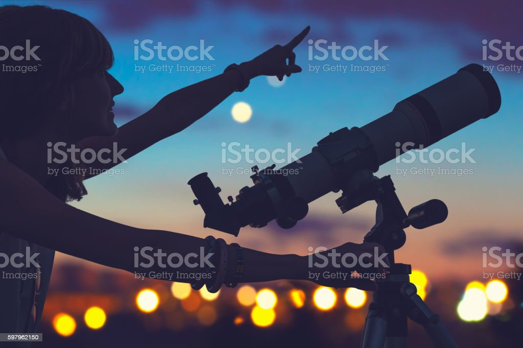 Girl looking at the stars with telescope beside her. stock photo