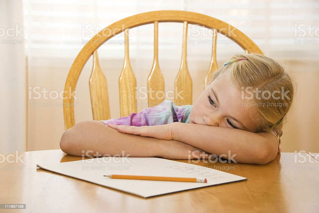 Girl looking bored at the table with her homework stock photo