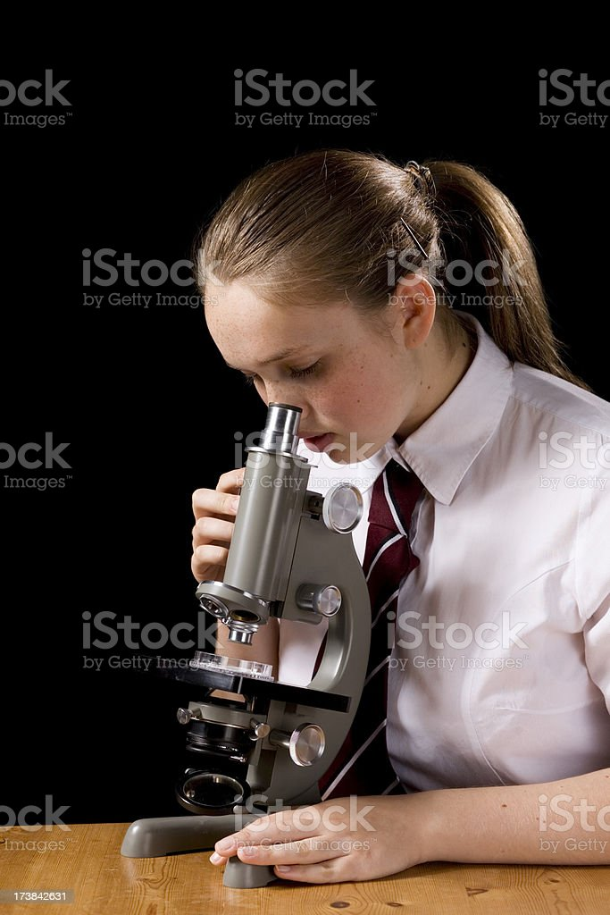 Girl looking down microscope on black royalty-free stock photo
