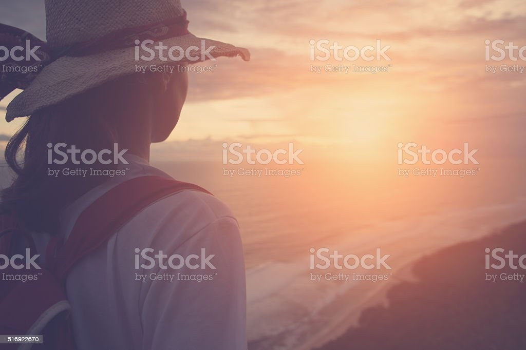 girl looking far away at sunset stock photo