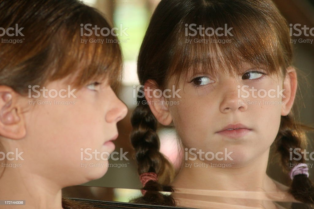 Girl looking in mirror royalty-free stock photo